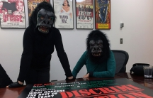 Two women in gorilla masks pose in front of their poster, which critiques the special months devoted to the history of marginalized groups.
