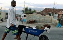 A Haitian with symptoms of cholera is transported in a wheelbarrow