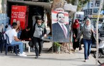 People walk next to a poster depicting Lebanon's Prime Minister Saad al-Hariri