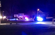 Blurry photo of residential neighborhood with police cars, lights