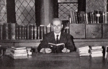 Black and white photo of man at table, with books
