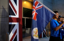 A campaigner carries a former colonial Hong Kong flag during a Hong Kong-UK reunification demonstration outside the British Consulate in Hong Kong on July 1, 2016, the 19th anniversary of Hong Kong's handover to Chinese sovereignty from British rule.