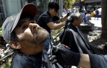 """A volunteer from the social work community """"Friends of the World"""" trims the beard of a homeless man in San Jose, Costa Rica February 24, 2016."""