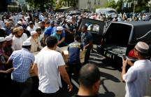 A crowd of community members move the coffin of Imam Akonjee