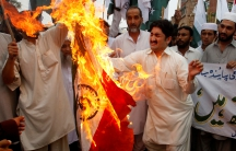 Pakistani protesters burn an Indian flag