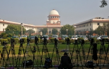 A television journalist sets up his camera inside the premises of the Supreme Court