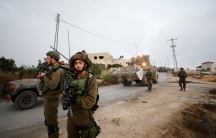 Israeli soldiers stand guard during the demolition of the family house of Palestinian assailant Omar Alabed