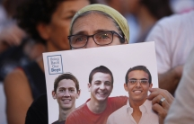 An Israeli woman holds a sign with images of three missing Israeli teenagers, at a rally in Rabin Square in the coastal city of Tel Aviv June 29, 2014. Israel on Thursday named two Hamas Islamists as leading suspects in the June 12 kidnappings of the thre