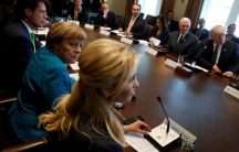 German Chancellor Angela Merkel sits to the left of Ivanka Trump, their backs facing the camera as they address President Donald Trump and a full table of German and American business leaders during a roundtable conversation at the White House on March 17