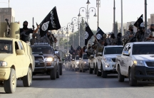 Militant Islamist fighters parade on military vehicles along the streets of northern Raqqa province on June 30, 2014.
