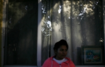Blurry image of woman in pink hodded sweatshirt standing in front of window, with reflection of trees