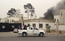 Armed men aim their weapons from a vehicle as smoke rises in the background near the General National Congress in Tripoli May 18, 2014. Heavily armed gunmen stormed into Libya's parliament on Sunday after attacking the building with anti-aircraft weapons