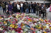 People look at floral tributes for the victims of the attack on London Bridge and Borough Market near the scene of the attack, London, June 6, 2017.