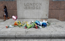 A woman passes flowers left on the south side of London Bridge
