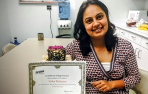 Woman sitting at table holding certificate, smiling