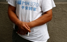 A man surnamed Lee who said his son was aboard the Malaysia Airlines flight MH370 that went missing in 2014 smokes during a protest outside the Chinese foreign ministry
