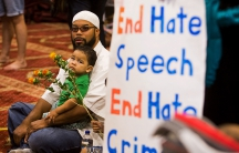 """Attendees sit next to a poster as speakers from different faiths speak at an interfaith rally titled """"Love is Stronger than Hate"""" at the Islamic Community Center in Phoenix. The rally was held in response to an earlier anti-Muslim rally at the same locati"""