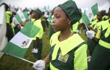 A school girl holds a Nigerian flag as she joins a parade marking Nigeria's 54th Independence Day in Lagos October 1, 2014.