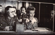 The interpreters' booth at the Nuremberg trials. From left to right: Capt. Macintosh, British Army, translates from French into English; Miss Margot Bortlin, translates from German into English; Lt. Ernest Peter Uiberall, Monitor.