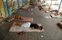 Palestinians, who fled their houses during an Israeli offensive, sleep at a United Nations-run school, sheltering displaced Palestinians, in Gaza City August 3, 2014.
