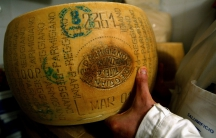An Italian grocer shows off his Parmesan cheese