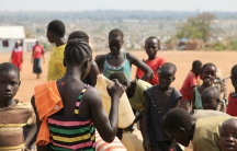 Refugees at Bidi Bidi refugee settlement in Uganda fill jerrycans at the water tank.