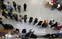 Voters stand in line in a lobby