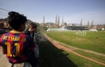 Roma community boys sit on the wall around Riza Lushta stadium as they watch the Kosovo's superleague soccer match between KF Trepca '89 and KF Istogu in Mitrovica, Kosovo, April 3, 2016.