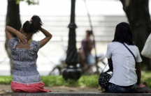 Cambodian sex workers wait for customers at a public park in Phnom Penh on July 20, 2010.