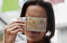 Martine Warren, a scientific advisor to the Bank of Canada, demonstrates how to view a security feature on the new polymer Canadian 100 dollar bill to reveal hidden numbers when pointed at a single point light source in Toronto November 14, 2011.