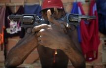 A Brazilian drug gang member nicknamed Pilintra, 26, poses with guns in Salvador.