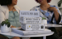 """Boxes on tables with labels: """"Safety pin box,"""" """"More than a safety pin,"""" """"Effective measurable allyship"""""""