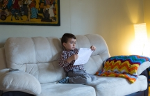 Boy sitting on cream sofa holding child's drawing, looking at it