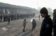 Migrants stand in line to receive free food outside a derelict customs warehouse in Belgrade