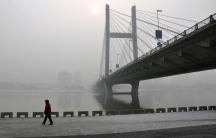 A resident walks along a street on the banks of the Songhua River near a highway bridge on a hazy day in Jilin, Jilin province, on February 25, 2014