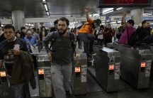 Demonstrators jump over the turnstiles without paying subway fare in support of a strike by metro workers in Sao Paulo June 9, 2014. Brazilian police used tear gas on Monday to disperse metro workers on strike in Sao Paulo in defiance of a court order to