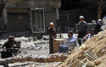 Residents receive food aid at the besieged al-Yarmouk camp,south of Damascus, April 24 2014, in this handout photograph distributed by Syria's national news agency SANA.