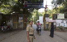 A security woman stands guard outside the Group of TB Hospitals in Mumbai, India