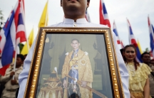 A well-wisher holds a picture of Thailand's King Bhumibol Adulyadej as he joins anti-government protesters gathering outside the Grand Palace on Coronation Day in Bangkok May 5, 2014.