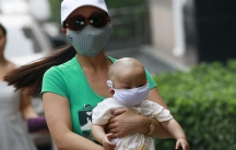 A woman carrying a baby, both wearing masks, make their way down a street and away from the site of explosions, in Tianjin, China.