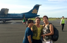 Mai, Tot and Ngoc Bich Ha, Cecilia Tran's mother, stand in front of an Vietnamese airplane.