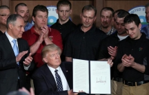 """A group of miners wearing black polos and several onlookers watch President Donald Trump as he holds up a signed version of his most recent executive order, """"Promoting Energy Independence and Economic Growth."""""""