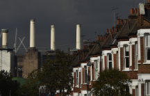 A rig (L) surrounds the top of one of the chimneys of Battersea Power Station as demolition work is carried out, in London, Oct. 2, 2014.