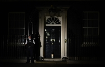 """A policeman stands guard as a lantern is placed at the front door of Number 10 Downing Street during """"Lights Out"""", as part of commemorations to mark the 100th anniversary of the outbreak of World War I on August 4, 2014."""