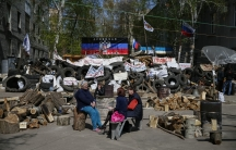 Pro-Russian protesters sit near barricades at the police headquarters in the eastern Ukrainian town of Slaviansk April 18, 2014. The self-declared leader of pro-Russian separatists in eastern Ukraine, Denis Pushilin, on Friday said that he did not conside