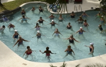 People take part in an aqua aerobics session in a swimming pool at a resort at Holetown, Barbados, March 7, 2014.