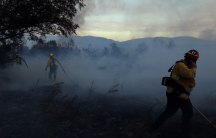 Firefighters work to put out hot spots on a fast moving wind driven wildfire in Orange, California, Oct. 9, 2017.