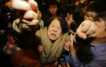 A family member of a passenger aboard Malaysia Airlines MH370 shouts at journalists at the Lido hotel in Beijing, March 24, 2014