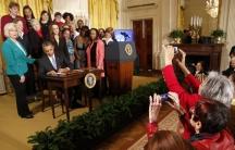 Women legislators take photos as US President Barack Obama signs two new executive actions