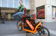"""Degheri coFounder Matt Saunders sits with the team's """"Cargo Bike"""" outside a shopping district in downtown Beirut, Degheri messengers are trying to attract clients by offering to bike their groceries home for them."""